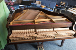 piano tuner Mark Mention with grand piano with lid and keys removed