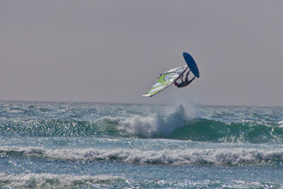a windsurfer flipping above the ocean